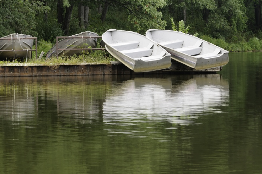 Boats of summer above water Pair of white rowboats on dock above reflecting lake
