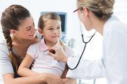 Mother with girl being examined by female pediatrician in clinic