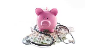 Piggy bank and stethoscope resting on pile of dollars on white background-1